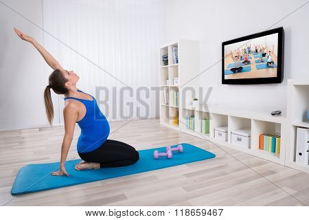 Pregnant Woman Exercising In Front Of Television