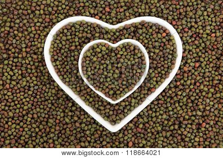 Mung beans in heart shaped porcelain dishes forming an abstract background.