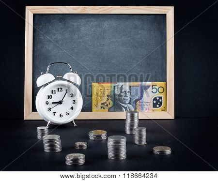 Vintage Clock, Blackboard, 50 Australian Dollars Bill, And Coin Towers On Black