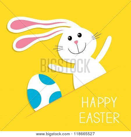 Happy Easter. Bunny Rabbit Hareand Blue Painted Egg In The Paper Pocket. Baby Greeting Card. Yellow