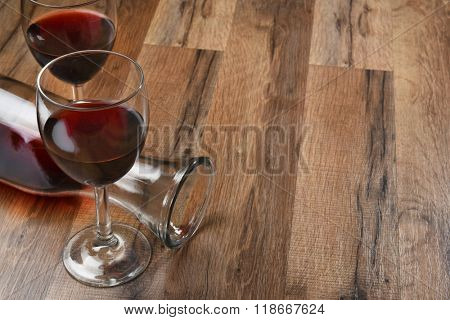 Top view of a carafe and two wine glasses on a wood table with copy space.