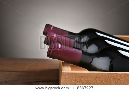 Three bottles of red wine in a wood crate with a light to dark gray background.