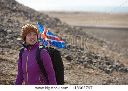 Woman traveller exploring hiking in stark icelandic landscape the iceland flag flapping in the wind