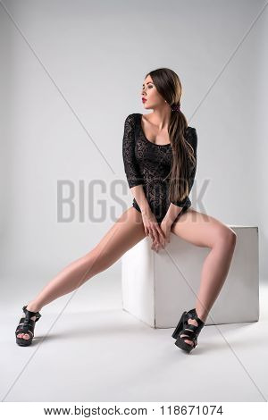 Leggy model wearing black bodysuit and high heels