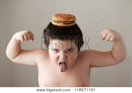 fat boy with  burger on  head showing muscles and   tongue