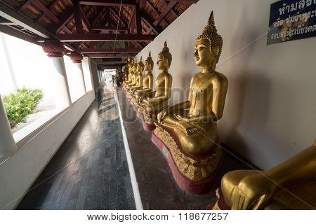 Row of golden Buddha statue in the cloister