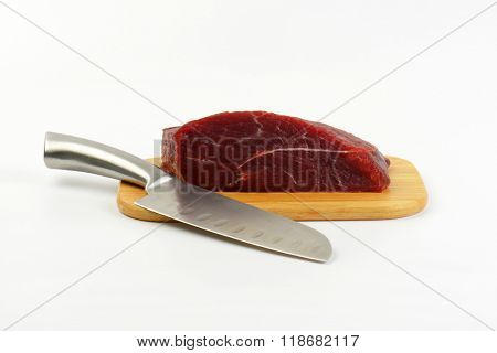 chunk of raw beef meat and sharp knife on wooden cutting board