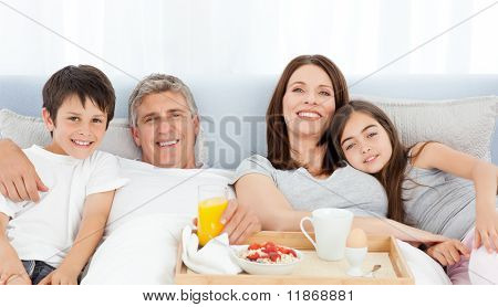Family Having Breakfast In Their Bed