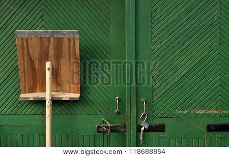 Wooden Snow Shovel In Fron Of Green Hangar Door.