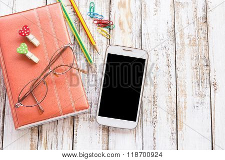 Blank Screen Smartphone With Pencil And Notebook On Table