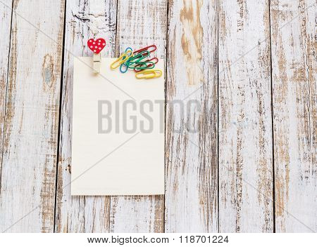 Paper And Paperclip On Wooden Table