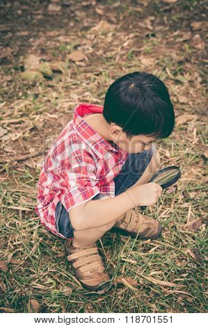 Young Boy Exploring Nature With Magnifying Glass. Outdoors. Vintage Style.