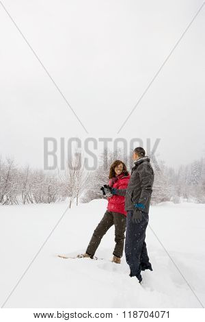 Mature couple walking through snow