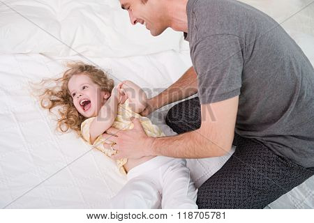 father tickling his daughter