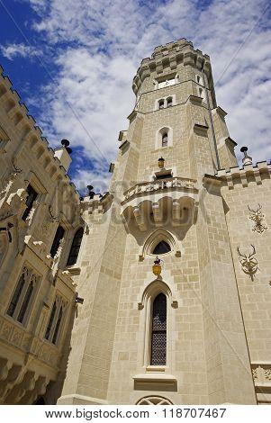 Tower of white fairytale castle high on the sky Hluboka castle Czech Republic