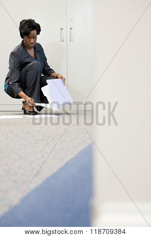 Businesswoman picking up paper