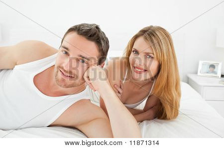 Couple Lying Down Together In Their Bed