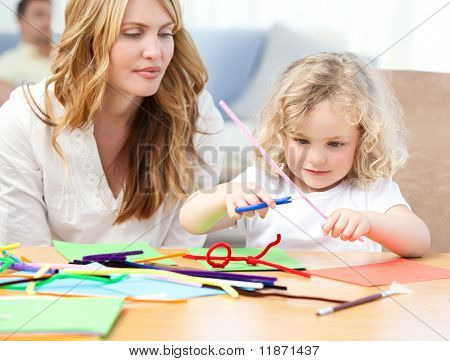 Woman And  Her Daughter Cutting Paper
