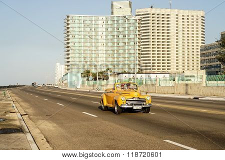 Yellow Vintage American Car In Front Of Two Hotels