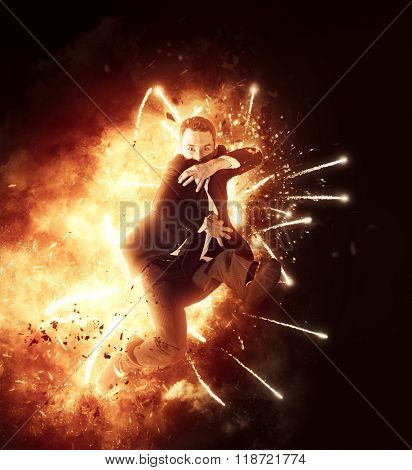 Businessman demonstrating power, energy and ambition as he bursts through a ring of fiery flames and sparks with his hand extended towards the camera