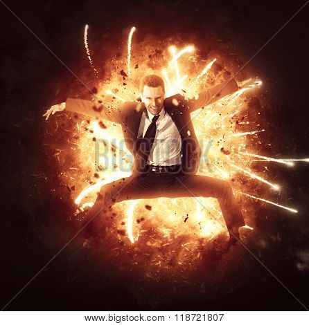 Angry aggressive businessman bursting through a circle of fiery flames with outstretched arms and a determined expression in a conceptual image