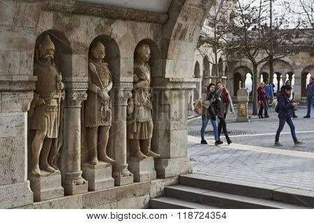 BUDAPEST, HUNGARY - FEBRUARY 02: Stone soldiers in one of the arches at Fisherman's Bastion, in the Old Town district, with tourists passing by in the background. February 02, 2016 in Budapest.