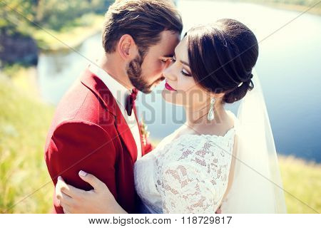 Bride and groom, lovely couple, cuddling on waterfront, photo shoot after wedding ceremony. Stylish