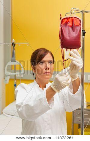 Nurse in hospital with blood bottle.