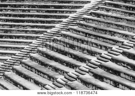 Old Amphitheater Texture Covered By Snow. Amphitheater Background Seats Covered By Snow In Winter..
