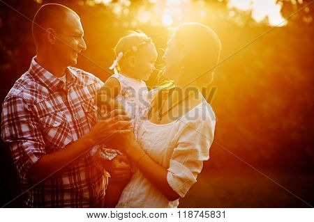 Young Family With Little Daughter Walking In The Park At Sunset