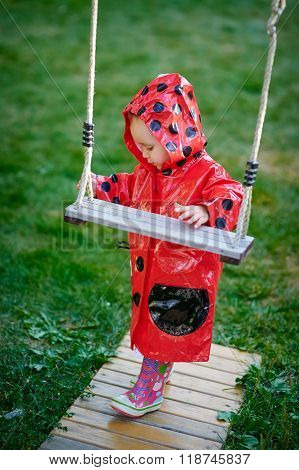 Little Girl In A Red Jacket Stands Near The Swing