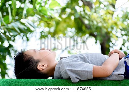 Boy Lay On The Green Lawn