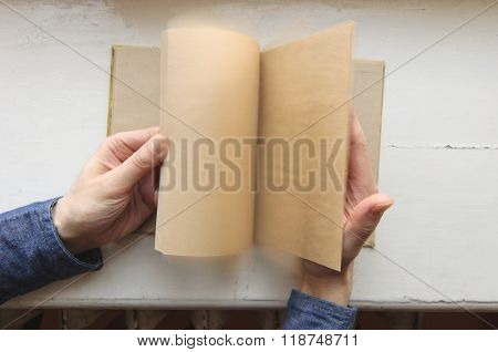 Person holding notebook and flipping pages on tabel