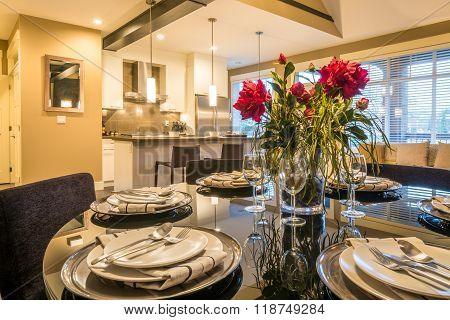 Modern round dining room table set for dinner in a luxury house with a kitchen in the background. In