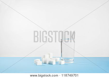 Glass of pure water and sugar, diabetes disease, sweet addiction on white background