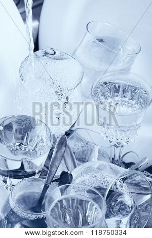Dishwashing - Glassware,cutlery and dishes under a water jet in the kitchen sink