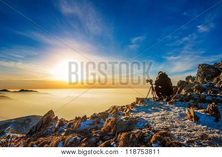 Professional Photographer Takes Photos With Camera On Tripod On Rocky Peak At Sunset.