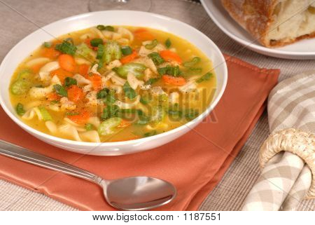 Closeup Of A Bowl Of Chicken Noodle Soup With Rustic Bread