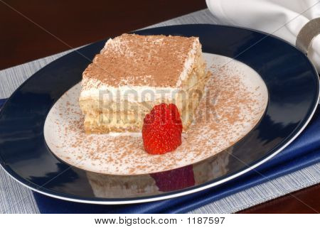 A Piece Of Tiramisu Dusted With Cocoa On A Blue Plate