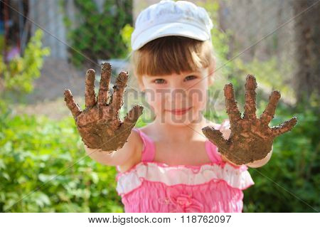 Girl shows her dirty hands.