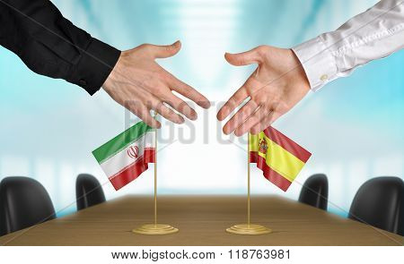 Iran and Spain diplomats shaking hands to agree deal