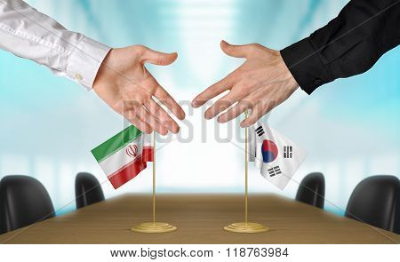 Iran and South Korea diplomats shaking hands to agree deal