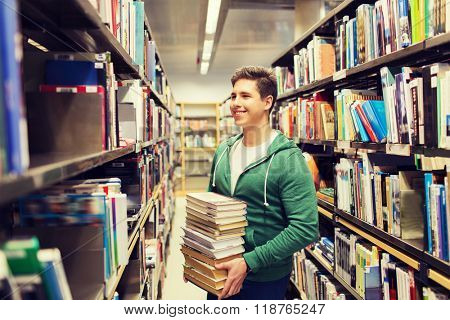 people, knowledge, education, literature and school concept - happy student or young man with book in library