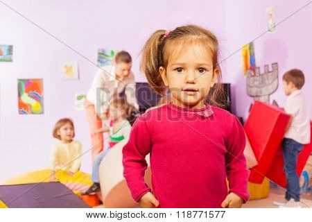 Portrait of nice little girl with group behind