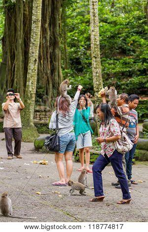 Ubud, Indonesia - January 23, 2013. Tourists Feed Monkeys In Monkey Forest. Ubud, Bali, Indonesia.