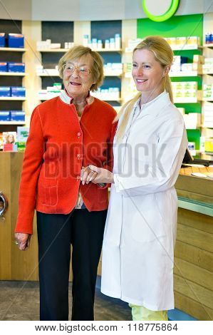 Pharmacist Holding Hand Of Customer
