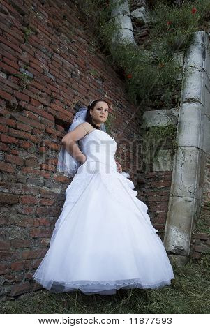 Young bride posing for the camera with large castle wall behind her