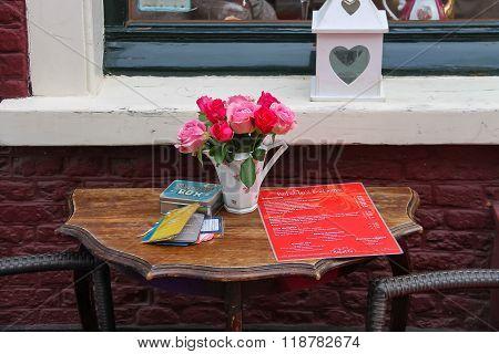 Outdoor Table With Roses In Vase And Menu Of Tea Rooms Bij Babette On Kruisstraat Street In Haarlem,