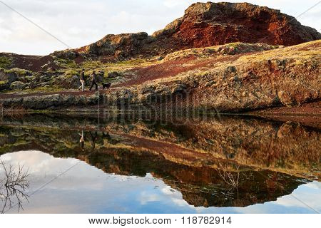 Couple walking their dog along a ridge beside a lake, reflection of them in the water