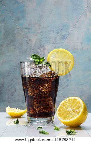 Glass Of Cola With Ice Cubes, Lemon Slices And Peppermint Garnish Against A Blue Vintage Wal
